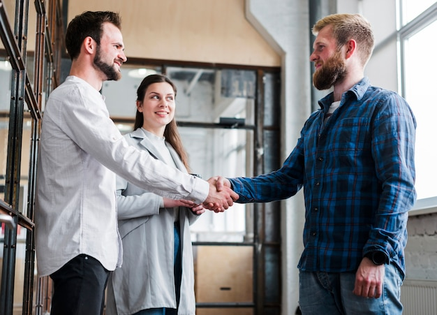 Two male coworker shaking hand in front of smiling businesswoman in office