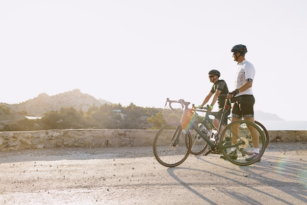 Two male cyclists stand on the coastal road and have a rest