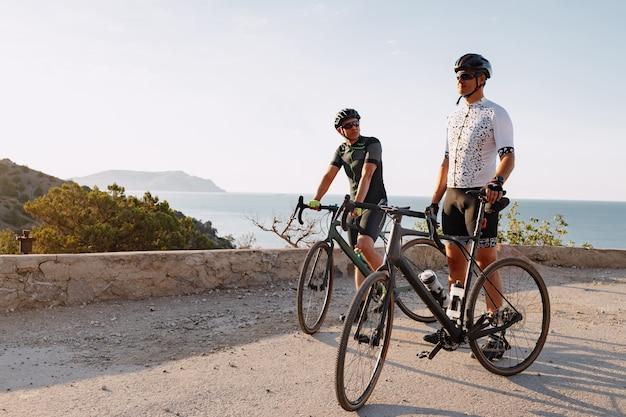 Два велосипедиста-мужчины стоят на дороге и отдыхают