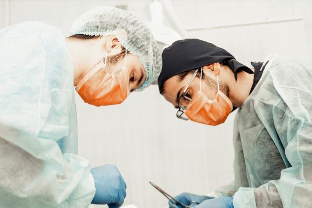 2人の男性歯科医が患者に手術を行います。歯科の手術。プロの制服と歯科医の機器。ヘルスケア医師の職場を装備する。歯科