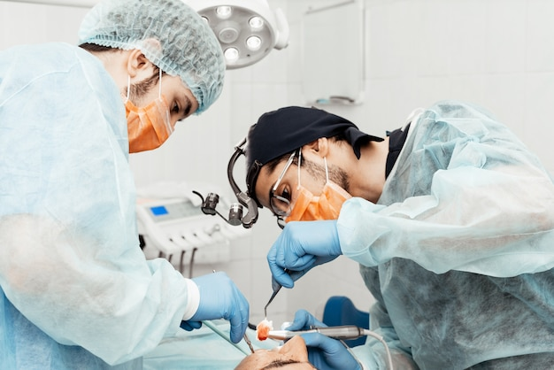 Two male dentists perform an operation on a patient. surgery in dentistry. professional uniform and equipment of a dentist. healthcare equipping a doctors workplace. dentistry