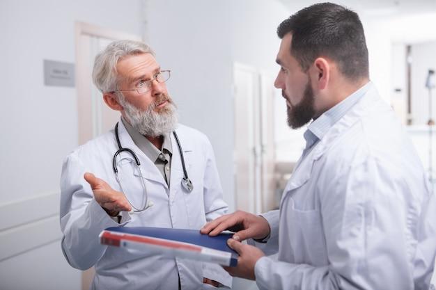 病院のホールでチャット2人の男性医師