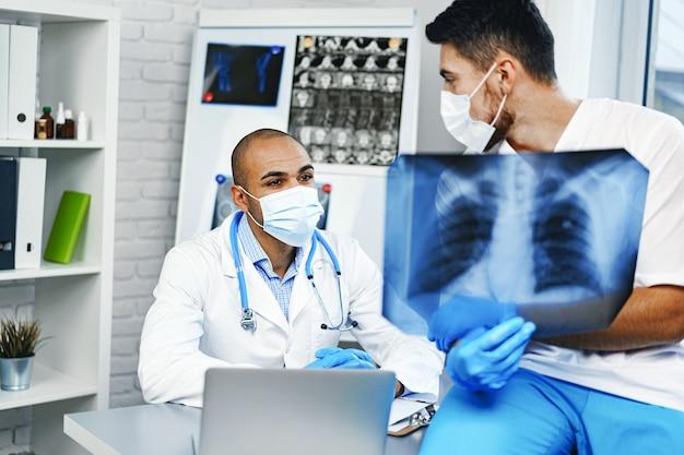 2人の男性医師が病院のキャビネットで肺のx線写真を検査します