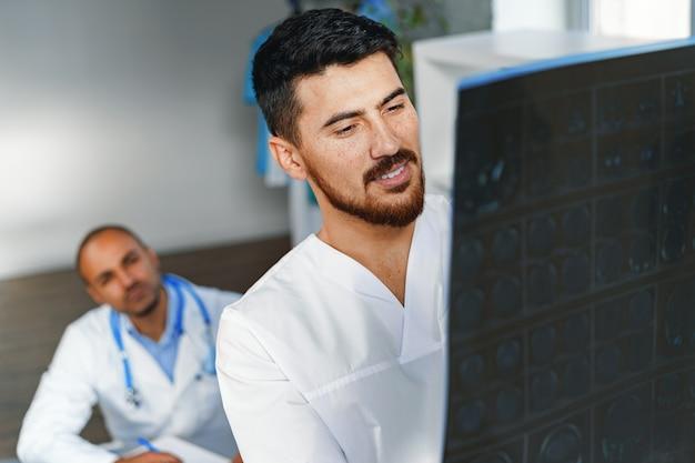 2人の男性医師が病院のキャビネットにいる患者のmri脳スキャンを検査します