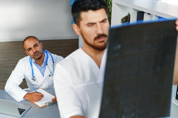 2人の男性医師がキャビネット内の患者のmri脳スキャンを検査します