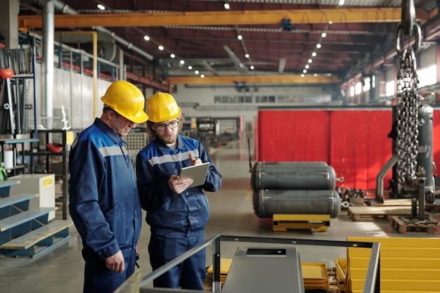 작업복을 입은 두 명의 남성 엔지니어가 큰 작업장이나 공장 한가운데 서서 새로운 산업 장비의 특성에 대해 논의합니다.