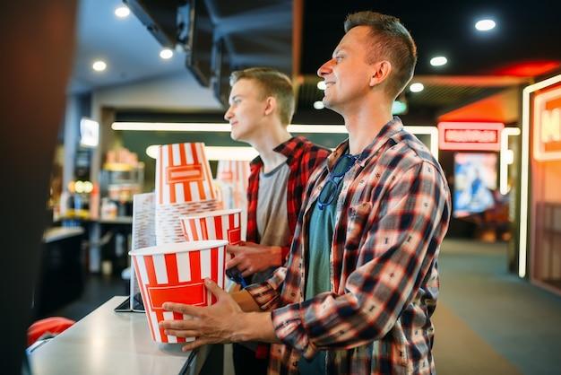 Двое друзей-мужчин покупают попкорн в кинотеатре перед началом сеанса.
