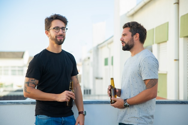 Two male friends drinking beer and talking