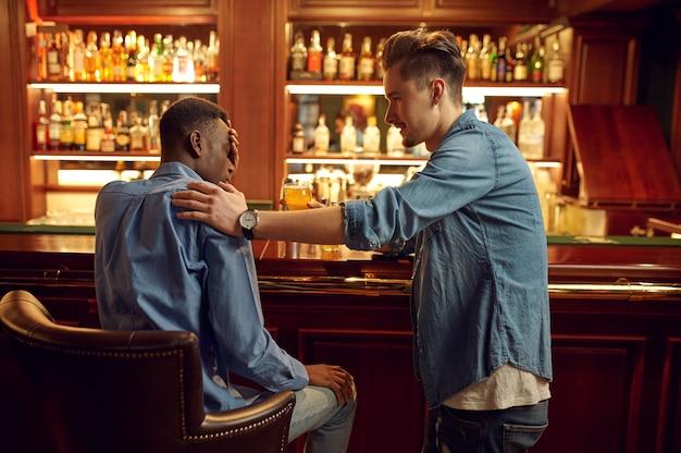 두 남자 친구는 바에서 카운터에서 맥주를 마신다