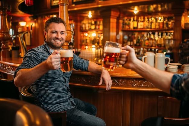 Двое друзей-мужчин пьют пиво за стойкой в пабе