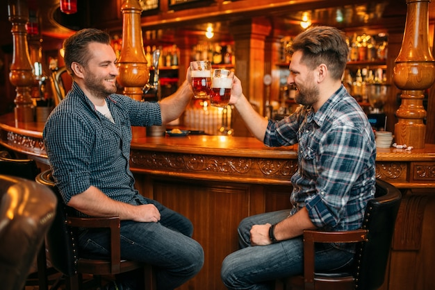 Two male friends drinks beer at the counter in pub