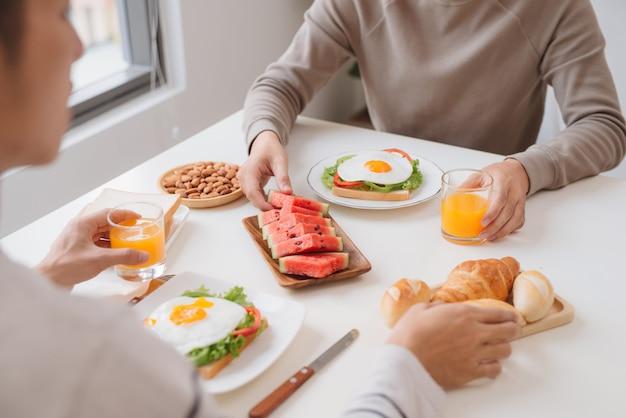Двое друзей-мужчин завтракают дома утром.