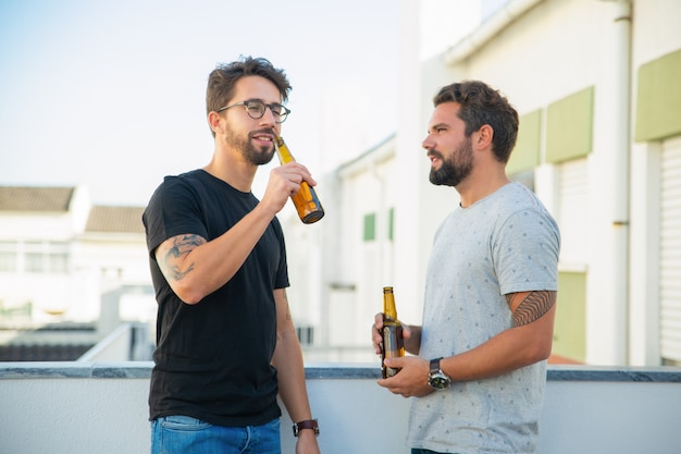 Two male friends enjoying party, chatting, drinking beer