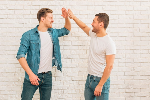Two male friends giving high five to each other against white brick wall