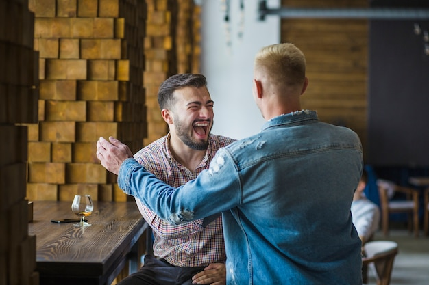 Two male friends having fun in the restaurant