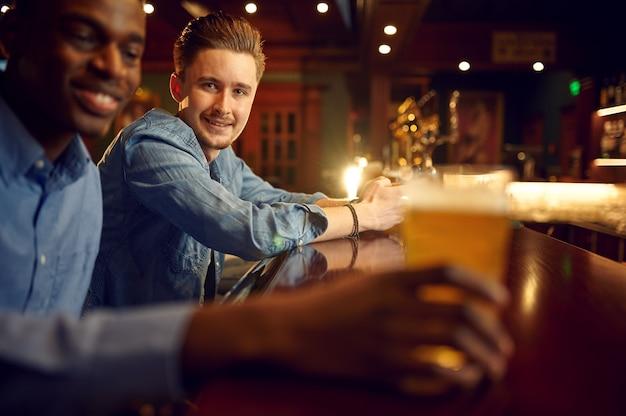바의 카운터에서 두 남자 친구 레저. 사람들의 그룹은 술집, 야간 라이프 스타일, 우정, 이벤트 축하에서 휴식을 취합니다.