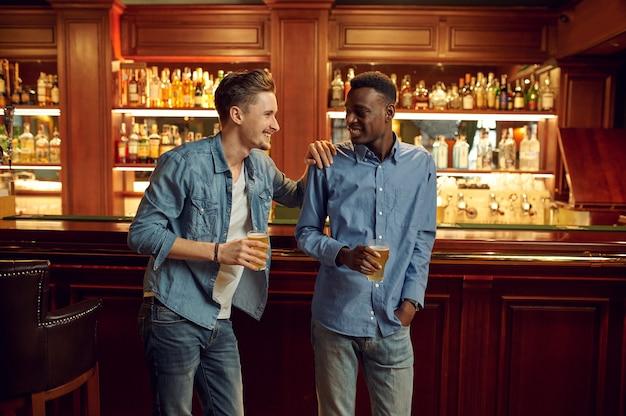 두 남자 친구가 바에서 카운터에서 맥주 잔과 함께 포즈. 사람들은 술집, 야간 생활, 우정, 행사 축하에서 휴식을 취합니다.