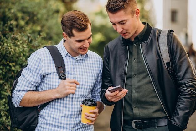 Двое друзей-мужчин студентов пьют кофе