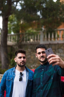 Two male friends taking selfie on mobile phone