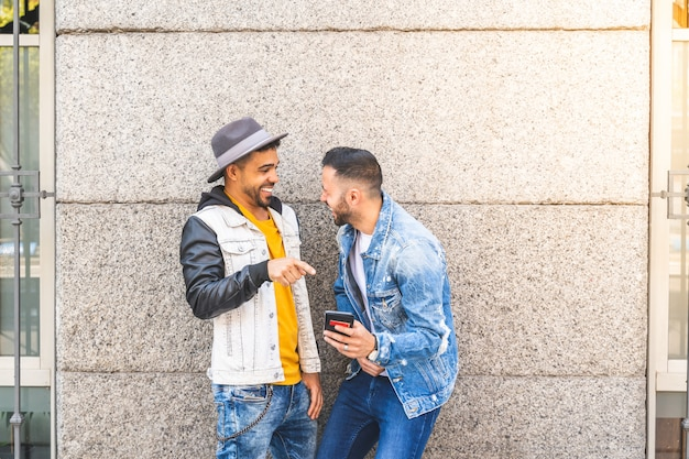 Two male friends using mobile phone outdoors while smiling.