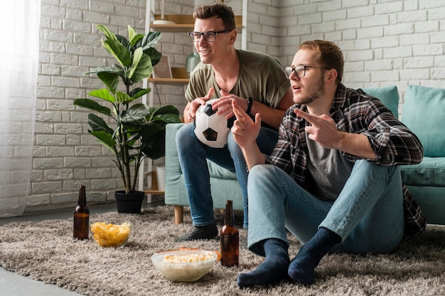 Two male friends watching sports on tv together while having snacks and beer