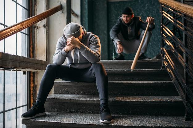 На лестнице сидят двое мужчин-гангстеров. уличные грабители с бейсбольной битой и ножом ждут жертву. понятие преступления