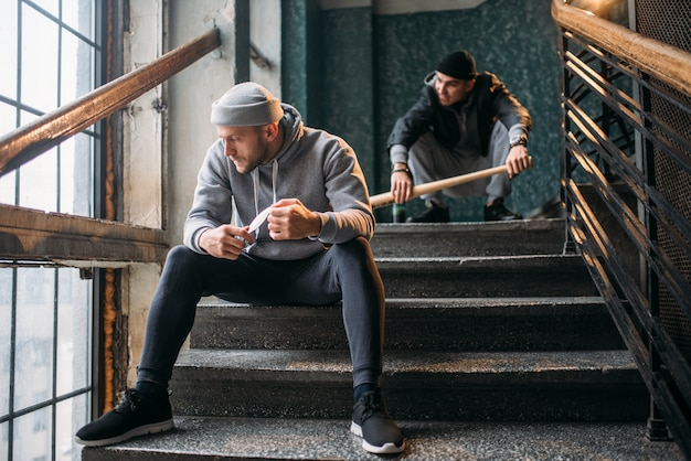 Two male gangsters are sitting on the stairs