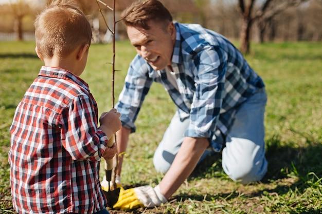 Два поколения мужчин работают в семейном саду и заботятся о пересадке дерева, засыпая почву компостом.