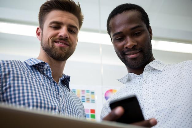 디지털 태블릿 및 휴대 전화를 사용하는 두 명의 남성 그래픽 디자이너