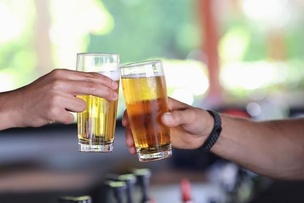 Две мужские руки держат стакан холодного пива и чокаются.