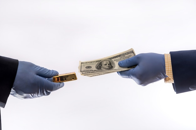 Two male hands in blue medical gloves with 100 dollar banknote, isolated. concept of corruption or ray at quarantine covid-19