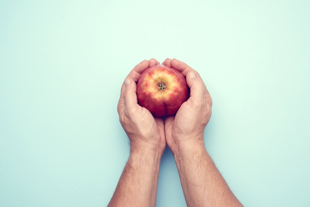 Two male hands hold a ripe red apple, top view