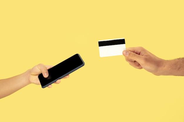 Две мужские руки держат мобильный телефон или смартфон и кредитную карту