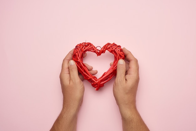 Two male hands holding a red wicker heart, love concept