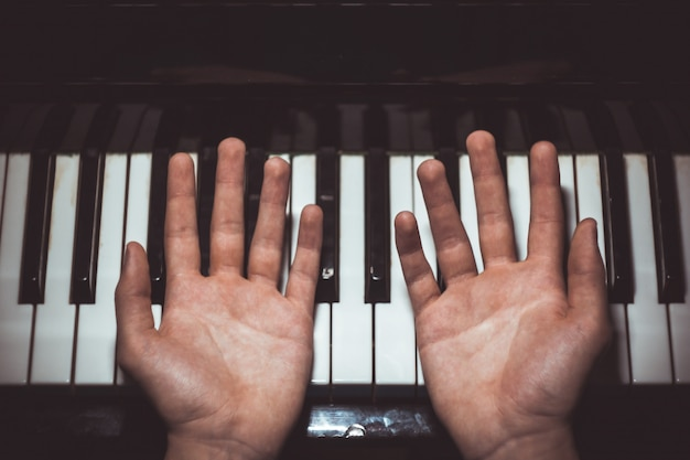Two male hands on the piano.