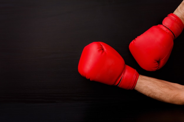 Two male hands in red boxing gloves on a black background on the side of the frame, place for text