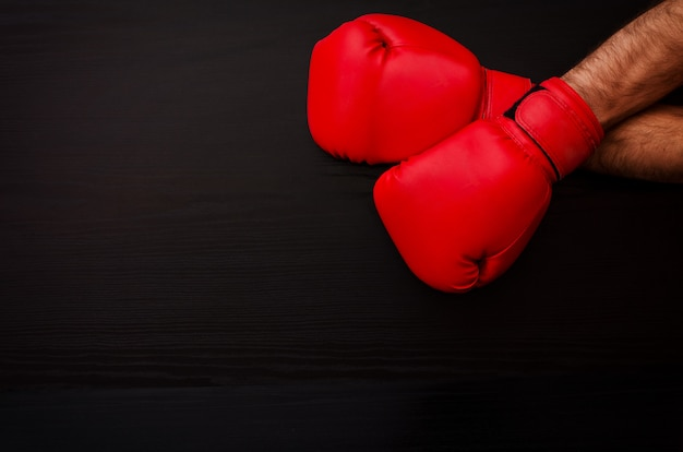 Two male hands in red boxing gloves on a black table