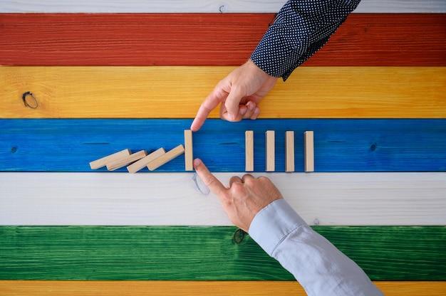 ドミノが概念的なイメージで崩壊するのを防ぐために一緒に働く2つの男性の手。木の板のカラフルな背景の上。