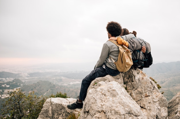 Два мужчины турист, сидя на вершине скалы над горой, глядя на живописный вид