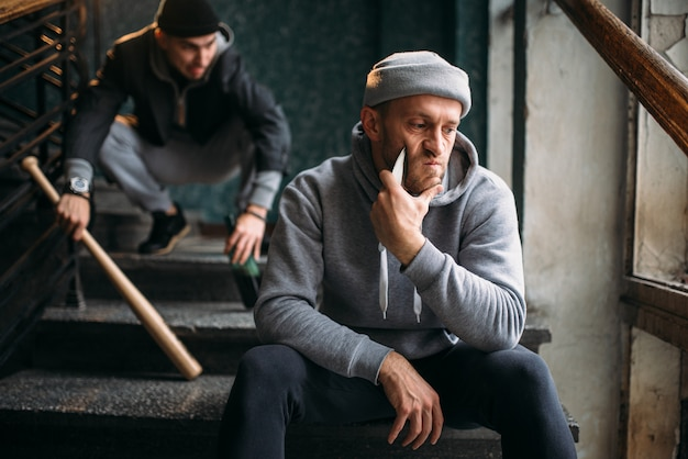 Two male hooligans are sitting on the stairs. street robbers with baseball bat and knife waiting for victim. crime concept
