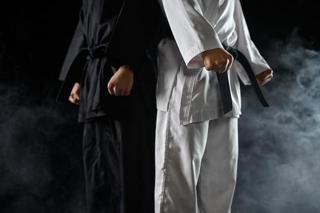 Два мужских каратиста в белом и черном кимоно. бойцы на тренировке, боевые искусства, боевые соревнования
