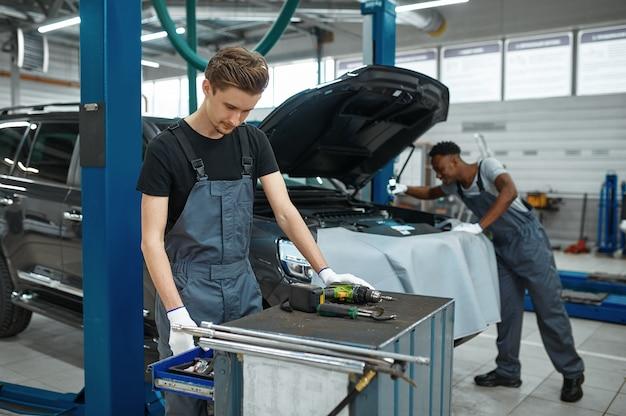 두 명의 남성 정비사가 엔진, 자동차 서비스를 검사합니다.
