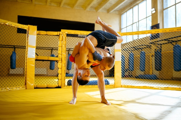 Two male mma fighters fights in a cage in gym.