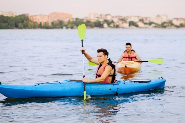 Two male paddling kayak on lake