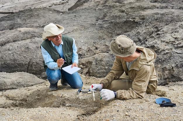 Двое палеонтологов-мужчин в пустыне обсуждают находку и делают записи в полевой тетради.