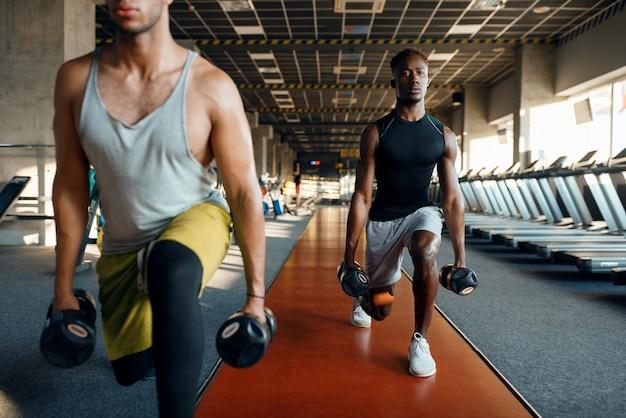 Двое мужчин делают упражнения с гантелями, тренируются в тренажерном зале