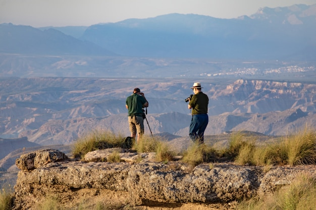 Two male photographers taking pictures of the gorafe desert in the light of sunset