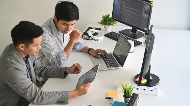 A two male programer working with laptop and coding on computer.