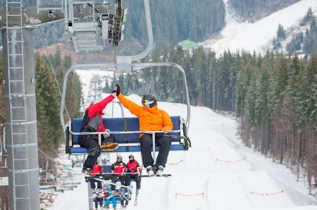Two male ride the ski chair lift up the mountain together