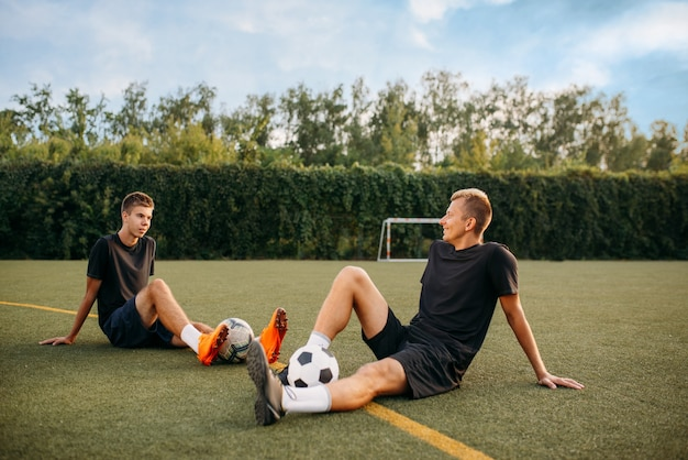 Two male soccer players resting on the grass on the field. footballers on outdoor stadium, workout before game, football training